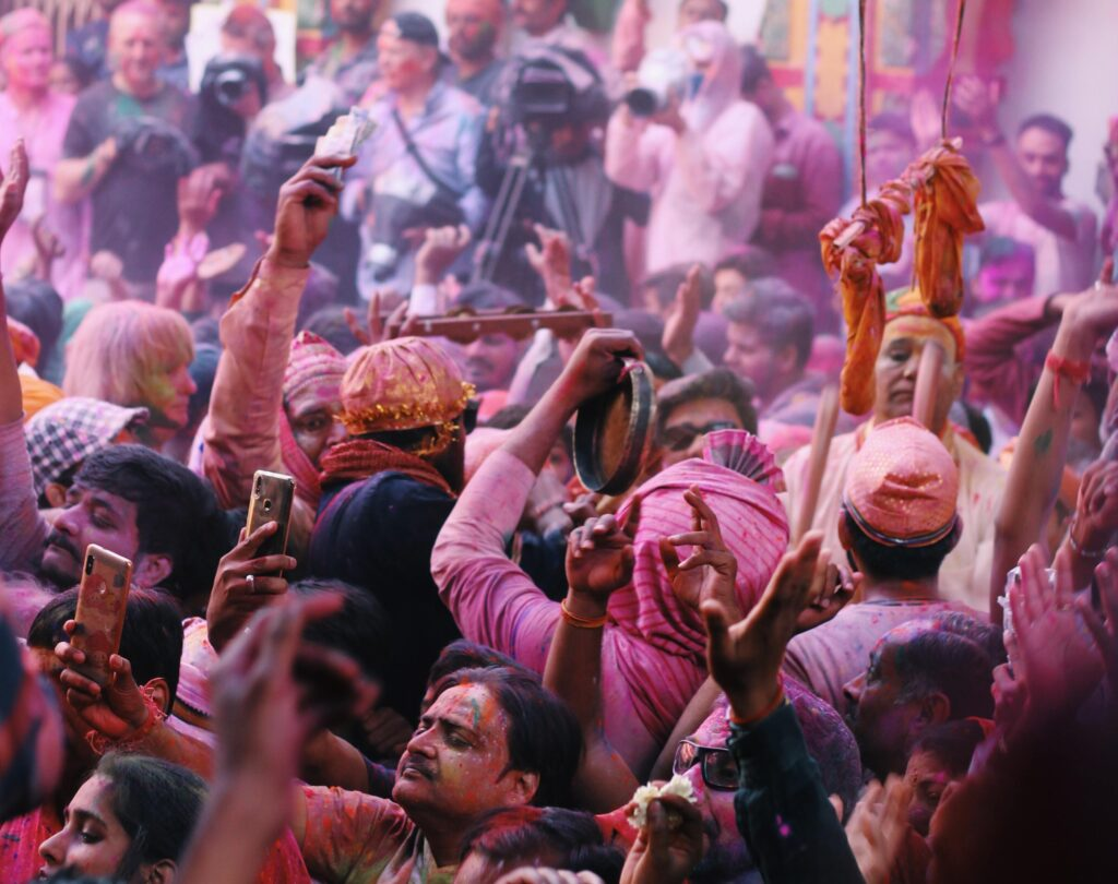 A crowd of people swathed in pink and red colours, many with their arms up. A turban-wearer plays the tambourine in the centre.